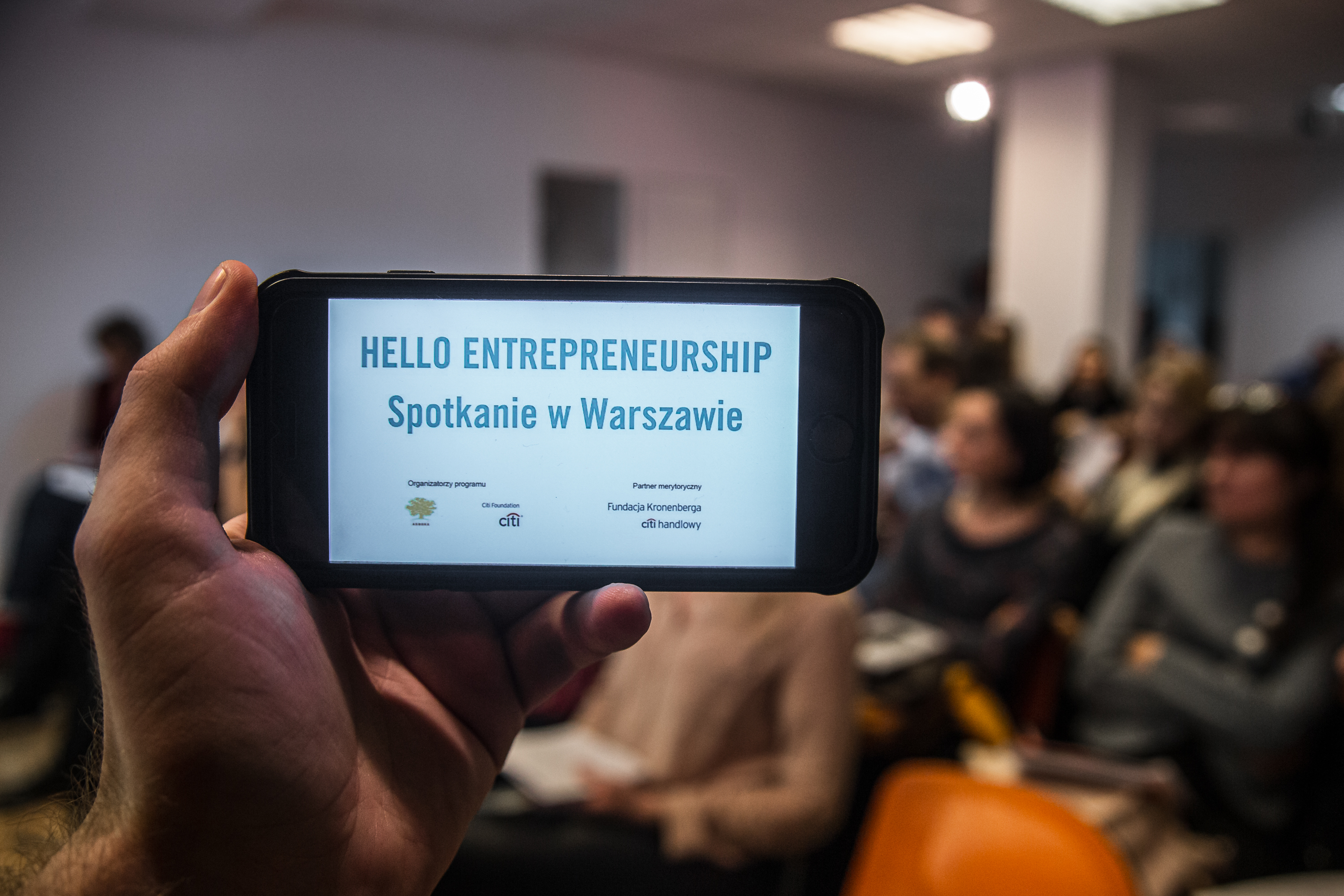 In the foreground a phone with text: Hello Entrepreneurship, in the background a room full of people