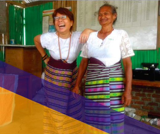 Two women wearing skirts of ethnic weaves laughing