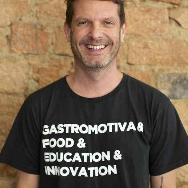 "White man smiling, with short hair and beard, and wearing a black shirt that says ""Gastromotiva & Food & Education & Innovation""."