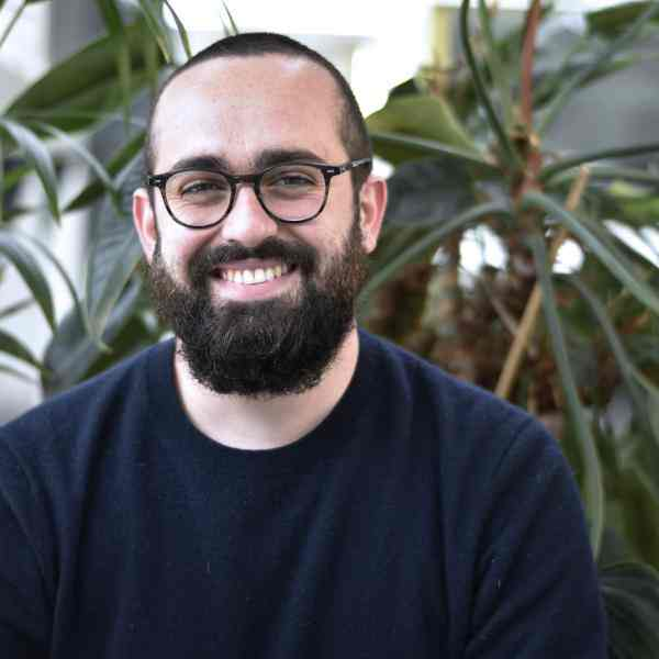 Photo of Félix Assouly; person with a beard and glasses and a dark blue sweatshirt. Background are a number of plants