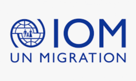 Logo of a world like icon. IOM UN Migration are the words next to the globe
