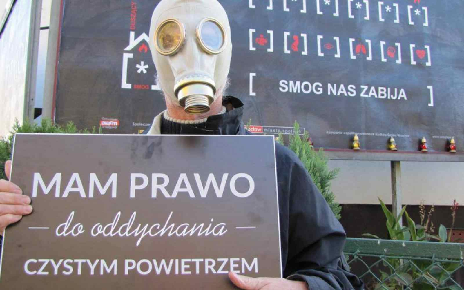 a person in a gas mask with a banner: I have a breath to breathe clean air