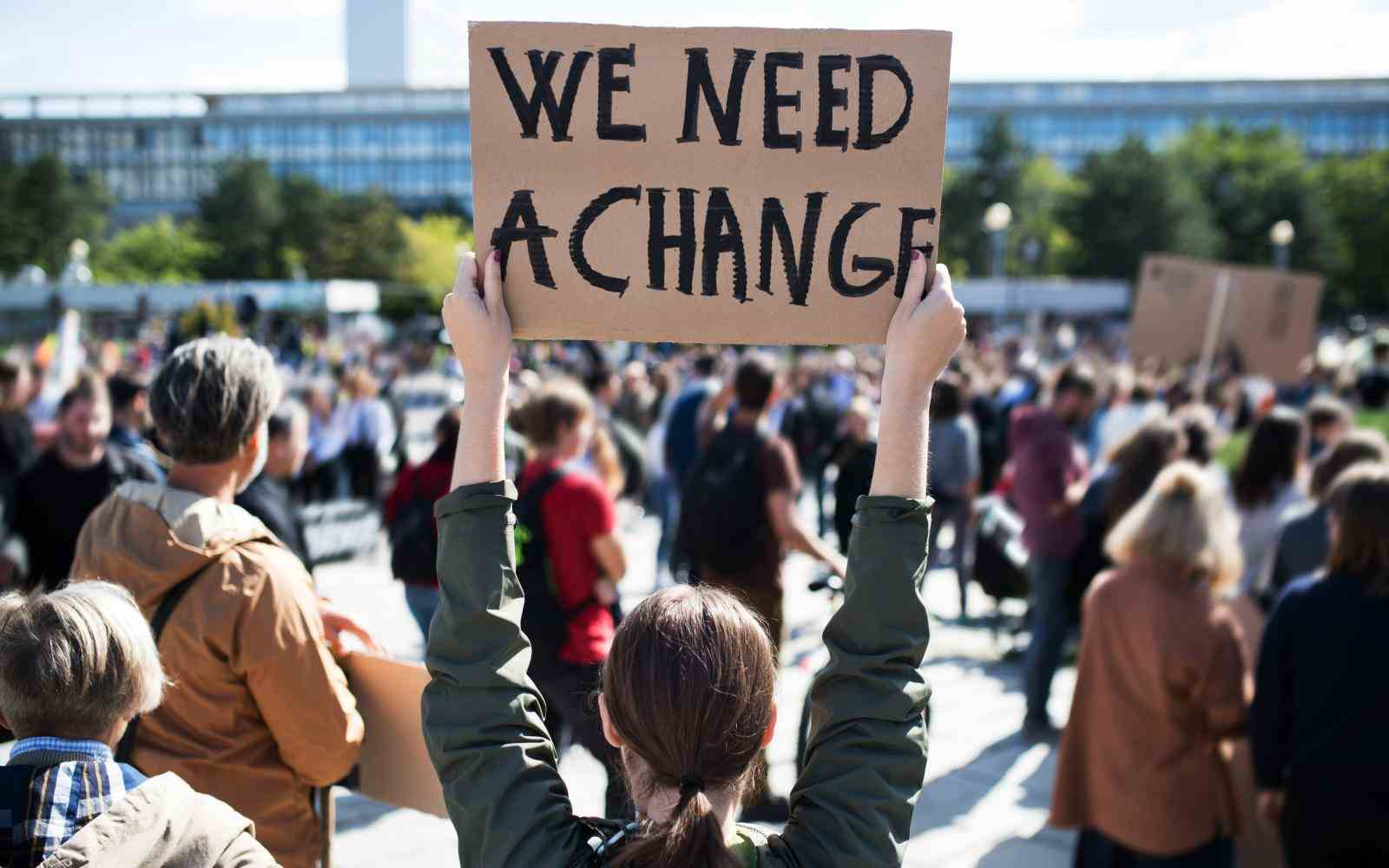 "Young person at a rally of climate activist holding a sign that says ""We need a change"""