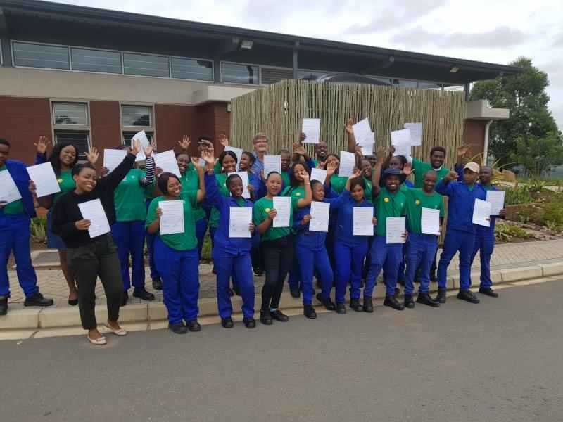 Group of smiling colleagues from South Africa holding up paper certificates