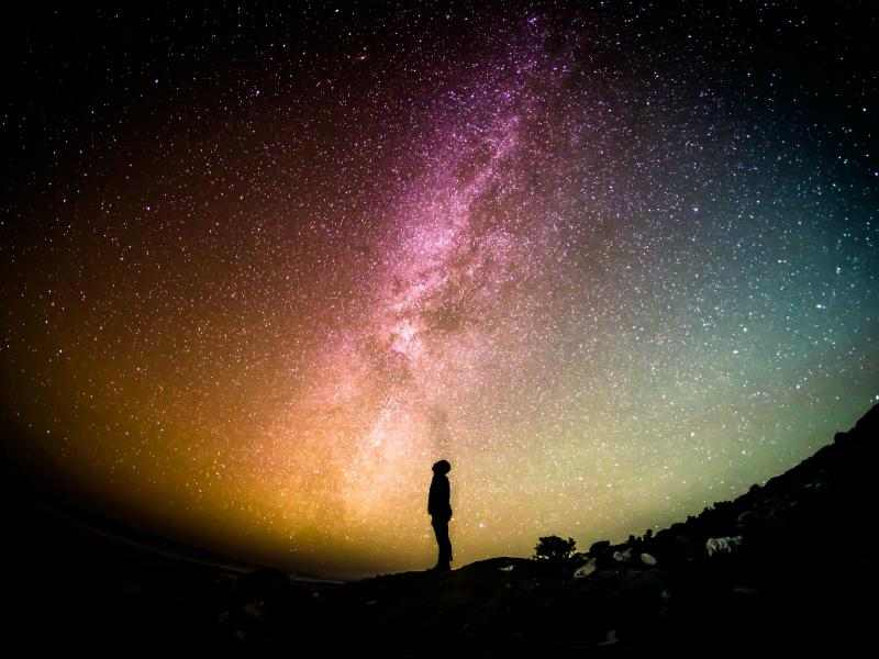 Person framed by a brightly colored sky and stars