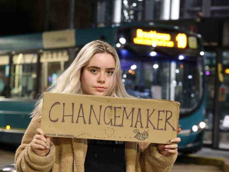 Liv holding a sign which says Changemaker