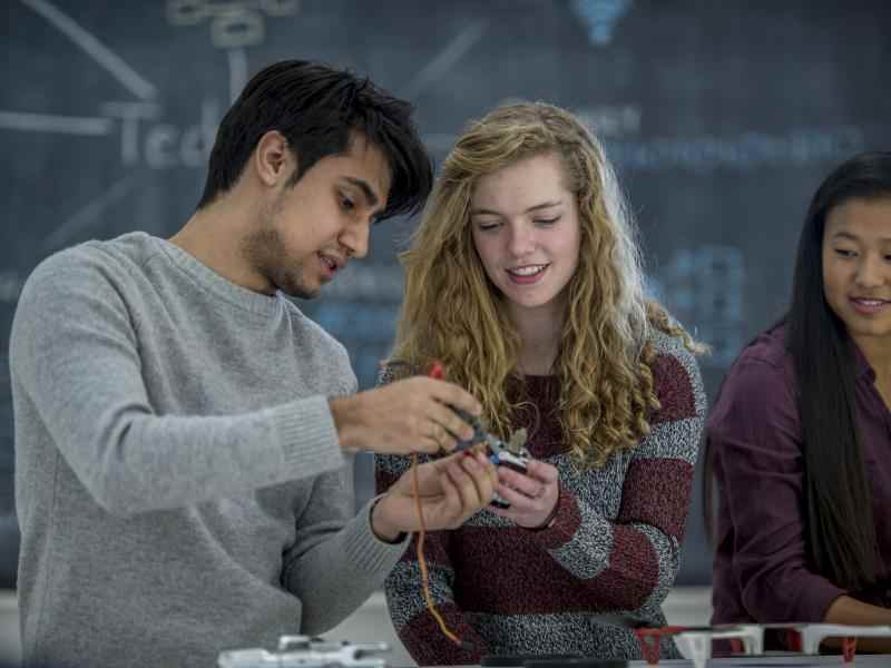 Two teens work together on a robotics project in science class