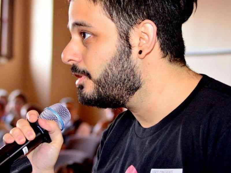 Lebanese man with a beard and a small pony tail holding a mic