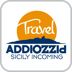 "Logo for Addiopizzo travel, Ashoka Italy (Italia) Partner; Orange circle like a sun over a city in solid blue; in the orange circle is the word ""Travel"" in white. underneath the city is the word Addiopizzo in capital dark blue letters, where Addio is left to right, and then Pizzo is upside down going right to left, sharing the o with Addio; underneath in smaller capital letters: ""Sicily incoming"""